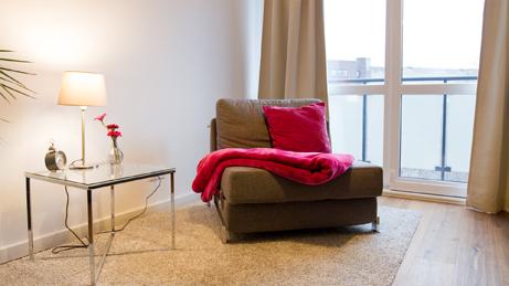 VillaroHome-Reinigungsservice: bequemer Sessel mit roter Kuscheldecke neben Glastisch vorm Fenster