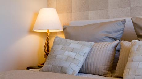 VillaroHome-Service: Wohnung möblieren - Bett mit vielen gemütlich Kissen neben Nachttisch mit eleganter Tischlampe